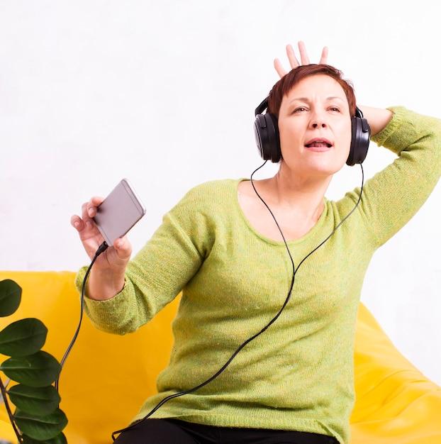 Música engraçada mulher sênior em fones de ouvido Foto gratuita