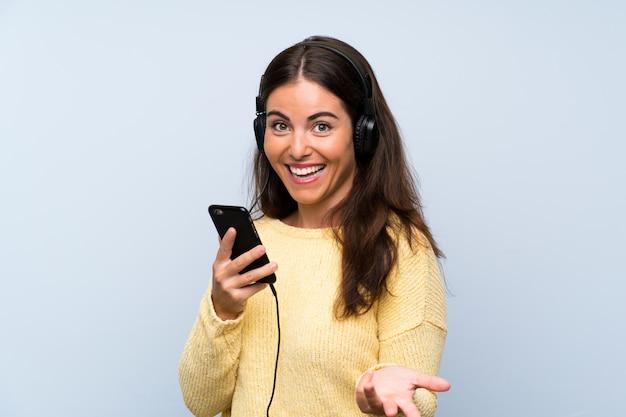 Música jovem com um celular sobre parede azul isolada Foto Premium