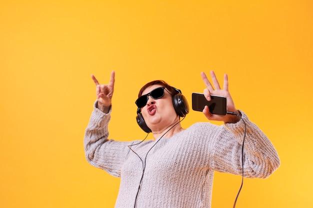 Música rock engraçada mulher sênior Foto gratuita