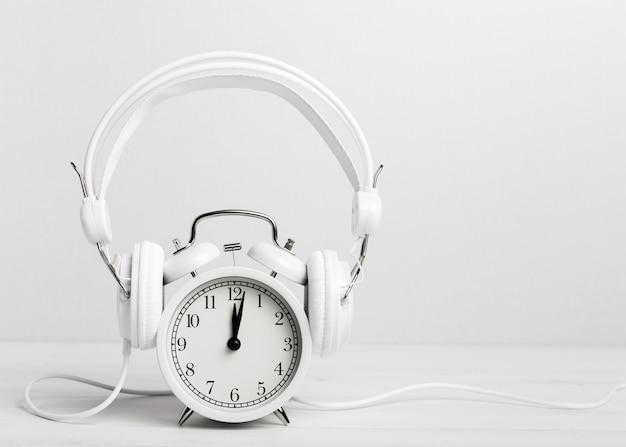 Música vintage relógio através de fones de ouvido Foto gratuita