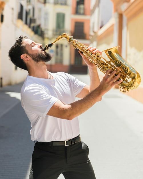 Músico apaixonado realizando na rua Foto gratuita