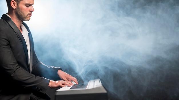 Músico artístico de vista lateral e efeito de fumaça azul Foto gratuita