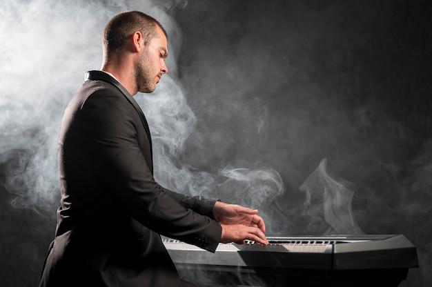 Músico artístico de vista lateral e efeito de fumaça Foto gratuita
