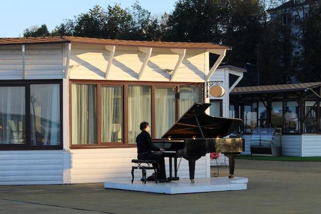 Músico de rua tocando piano de cauda à beira-mar na europa Foto Premium