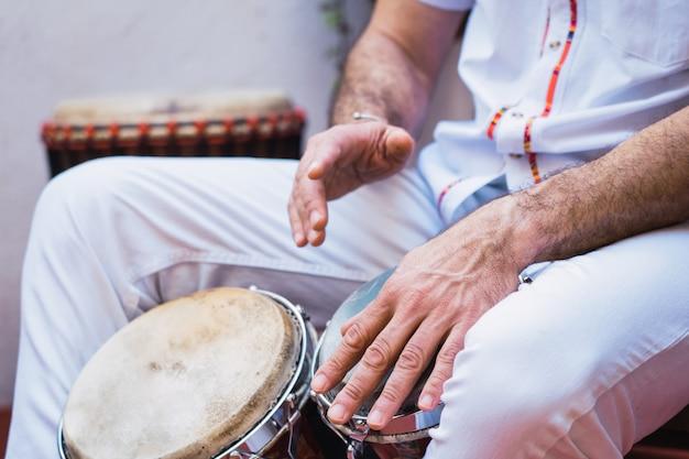 Músico de salsa tocando os bongos, um instrumento de percussão tradicional Foto Premium