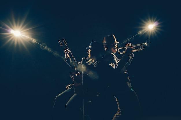 Músico duo banda tocando um trompete e cantando uma música e tocando guitarra no fundo preto wi Foto Premium
