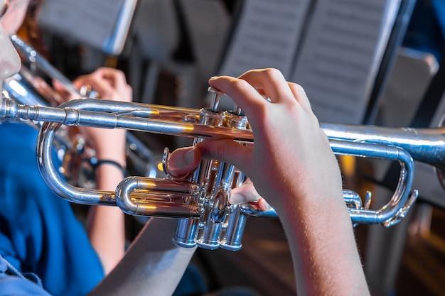 Músico masculino mãos segurando e tocando trompete em um concerto da banda local Foto Premium