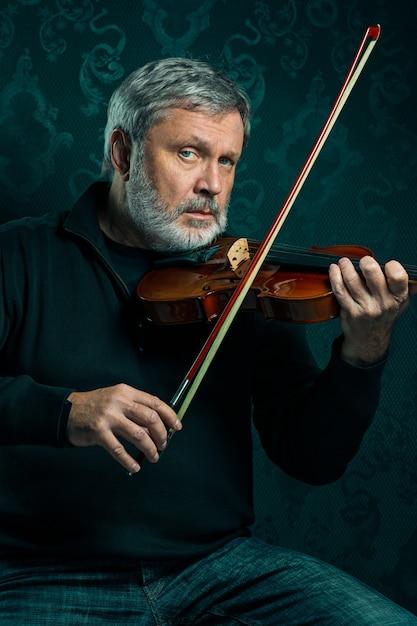 Músico sênior tocando violino com varinha em preto Foto gratuita