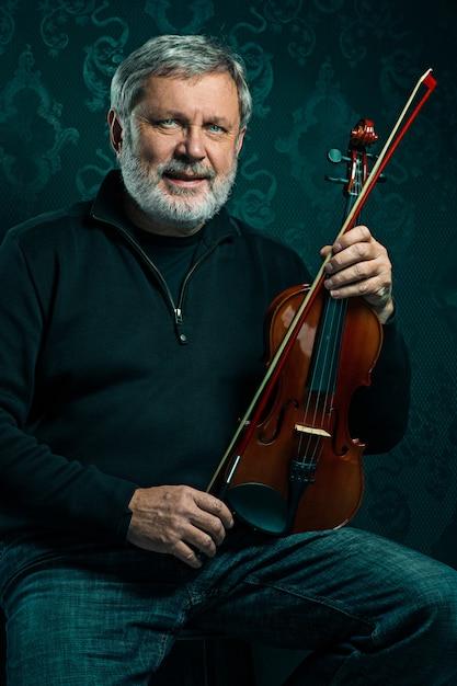 Músico sênior tocando violino com varinha na parede preta Foto gratuita