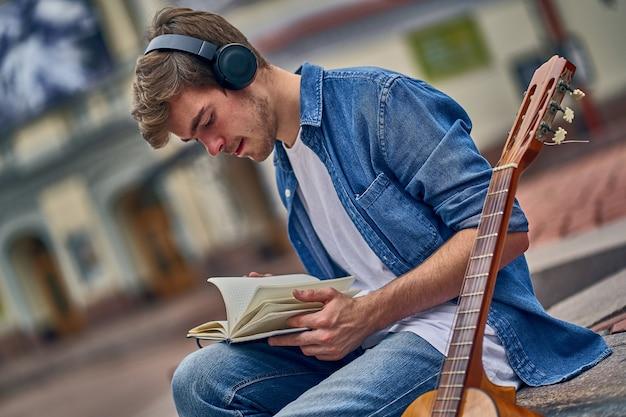 Músico talentoso e ocupado escreve uma nova música no caderno Foto Premium