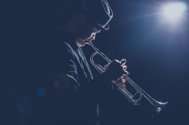 Músico tocando a trombeta com spot light e len flare no palco Foto Premium