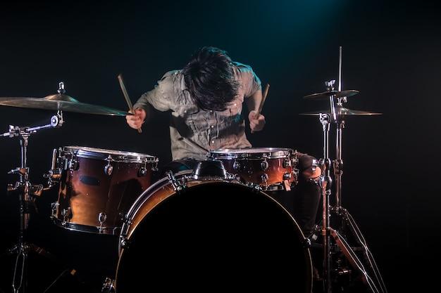 Músico tocando bateria, fundo preto e bela luz suave, jogo emocional, conceito de música Foto gratuita