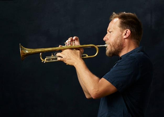 Músico veterano tocando trompete Foto gratuita