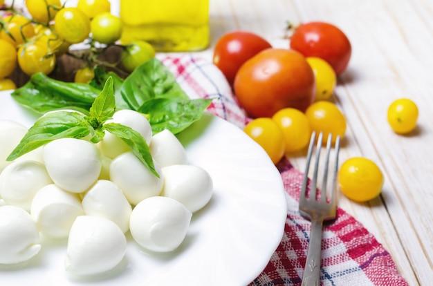 Mussarela fresca com tomate amarelo e manjericão. Foto Premium