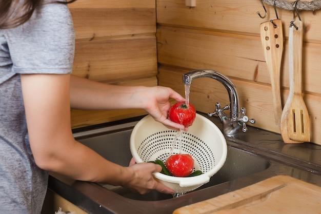 Na cozinha sob as mãos das mulheres de água corrente lave os tomates maduros Foto Premium