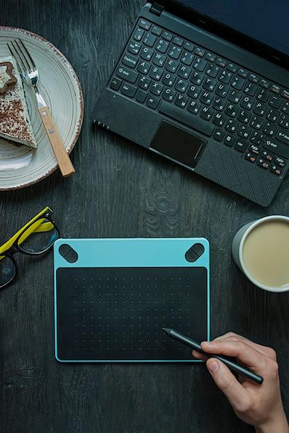 Na mesa há um laptop, uma mesa digitalizadora e uma xícara de café. Foto Premium