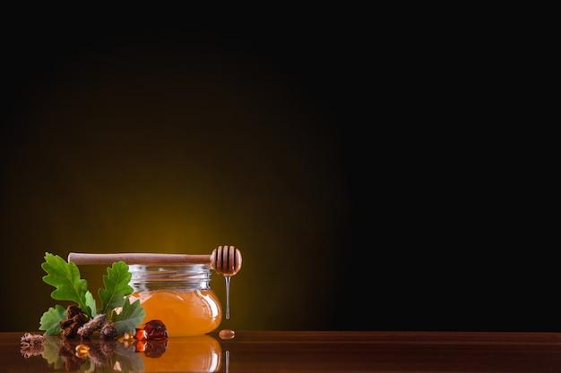 Na mesa há uma jarra de vidro com mel no escuro Foto Premium
