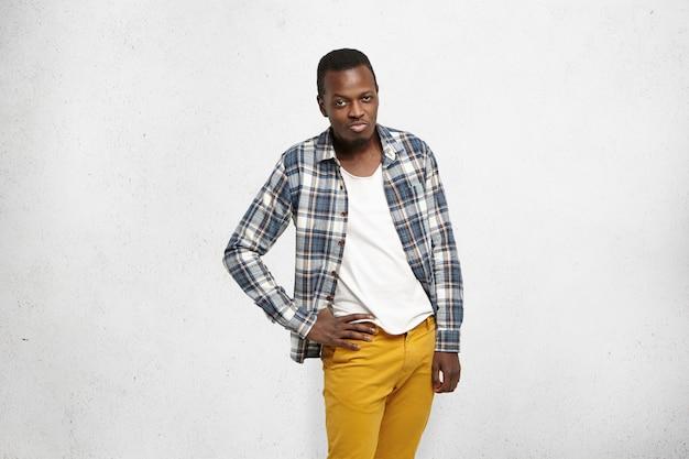 Na moda jovem afro-americano masculino vestindo calça jeans mostarda e camisa quadriculada sobre camiseta branca, segurando a mão no quadril, tendo olhar de paquera, atirando nos lábios como se estivesse tentando seduzir alguém Foto gratuita