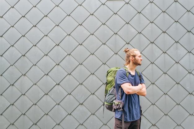 Na moda jovem com mochila de viagem a desviar o olhar Foto gratuita