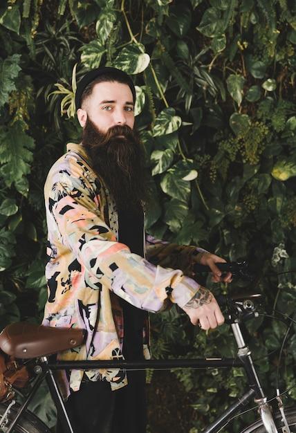 Na moda jovem com sua bicicleta em frente a planta Foto gratuita