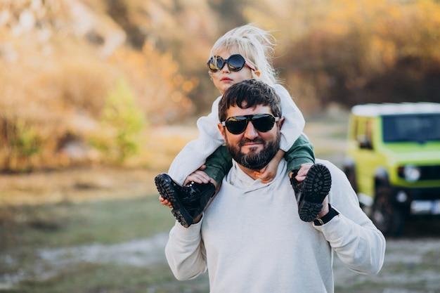 Na moda jovem pai com sua filha sentada nos ombros Foto gratuita