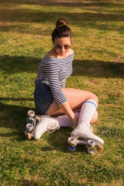 Na moda jovem vestindo patins sentado na grama verde Foto gratuita