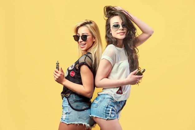 Na moda jovens amigos de óculos escuros e shorts de pé e fumar Foto Premium