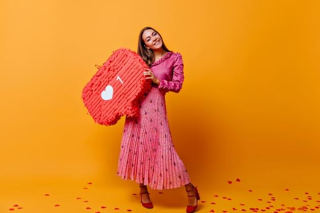 Na sala com parede de papelão laranja está uma elegante mulher de cabelos castanhos e saia longa, segurando um grande cartaz do instagram. foto tirada nas cores laranja e rosa Foto gratuita