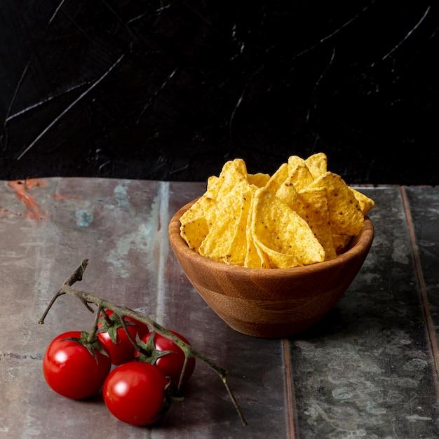 Nachos na tigela e ramo de tomate na mesa Foto gratuita