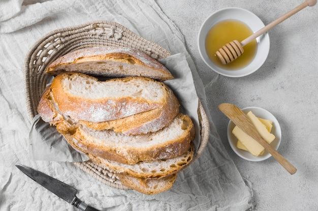 Nacos de pão em uma cesta com manteiga e mel Foto gratuita