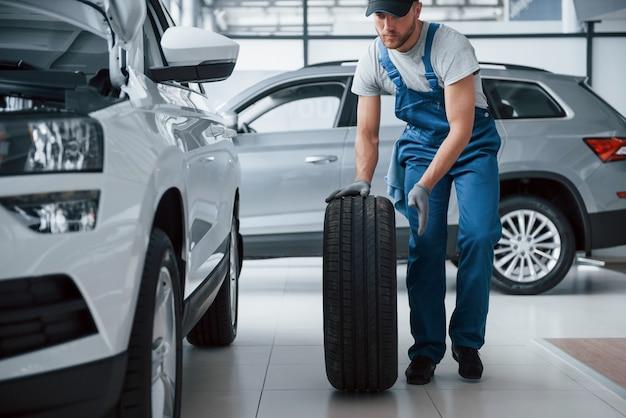 Nada demais. mecânico segurando um pneu na oficina. substituição de pneus de inverno e verão Foto gratuita