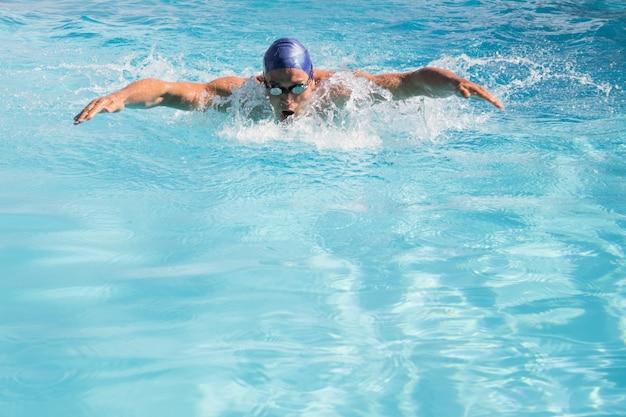 Nadador apto fazendo o curso de borboleta na piscina Foto Premium