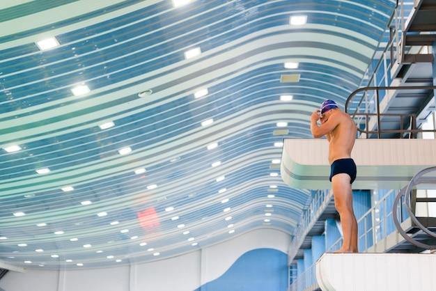 Nadador atlético do homem que prepara-se para saltar Foto gratuita