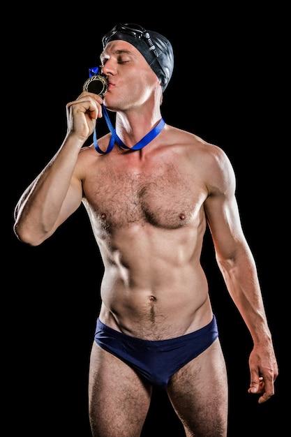 Nadador beijando sua medalha de ouro Foto Premium