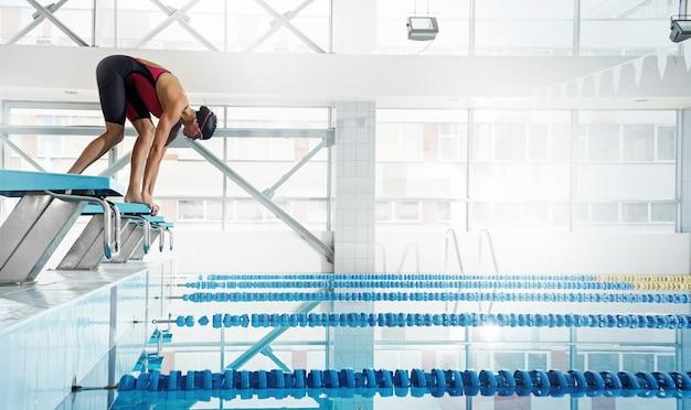 Nadador de mulher em uma posição inicial Foto Premium