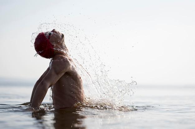 Nadador de tiro meio espirrando para fora da água Foto gratuita