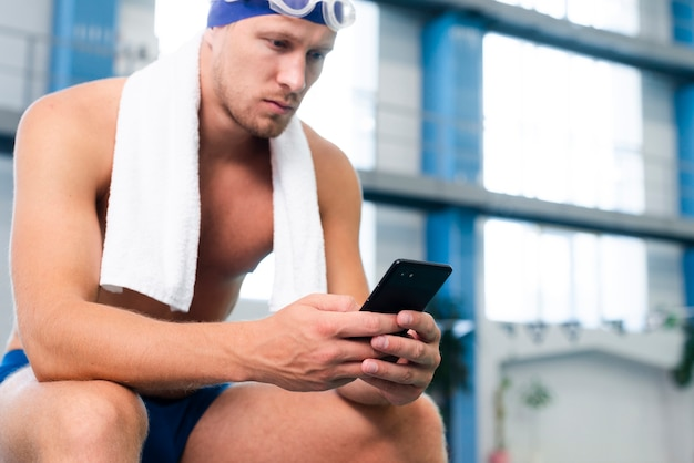 Nadador masculino de ângulo baixo, verificando móvel Foto gratuita