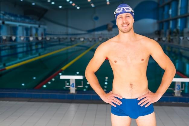Nadador masculino posando em frente a piscina Foto gratuita