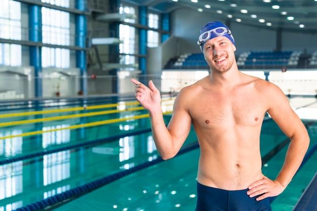 Nadador masculino sorridente, apontando o dedo Foto gratuita