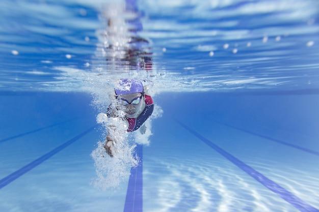 Nadador nadando na piscina. Foto Premium