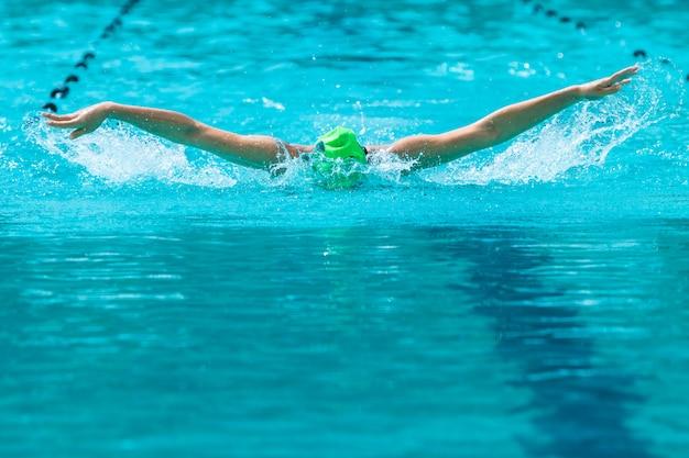 Nadadora trabalhando em seu curso de borboleta nadar em uma piscina local Foto Premium