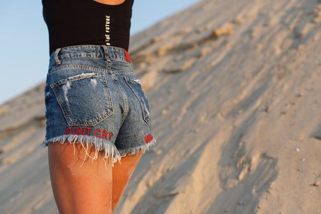 Nádegas femininas atraentes em suma na praia. garota sexy em shorts jeans ao ar livre. Foto Premium