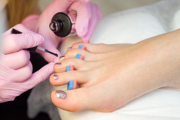 Nail care and pedicure concept. as mãos do manicuro do close up em luvas cor-de-rosa estão pintando o verniz para as unhas do ouro nos dedos do pé do cliente. Foto Premium