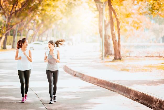 Namorada asiática saudável, movimentando-se juntos no parque Foto Premium