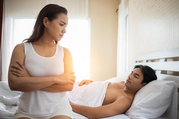 Namorada de tristeza sentar na cama pensar em problemas de relacionamento com o namorado Foto gratuita