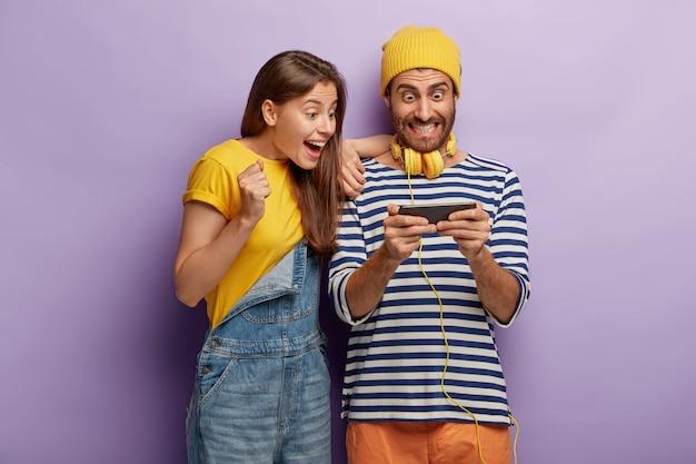 Namorada e namorado felizes curtindo o novo jogo, ficando satisfeito com os novos recursos do smartphone, olhando a tela do gadget, vestido com roupas da moda, torcendo para ganhar uma maratona online, sendo viciado Foto gratuita