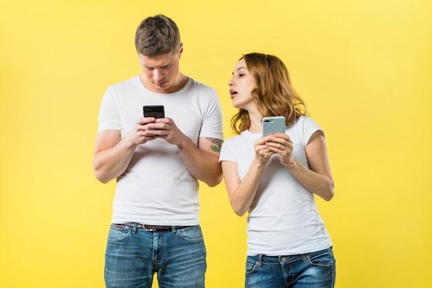 Namorada suspeita, espiando seu namorado, mensagens de texto no celular contra pano de fundo amarelo Foto gratuita