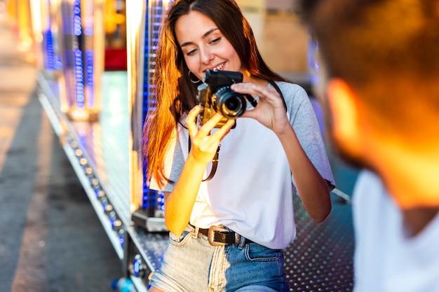 Namorada tirando foto do namorado na feira Foto gratuita