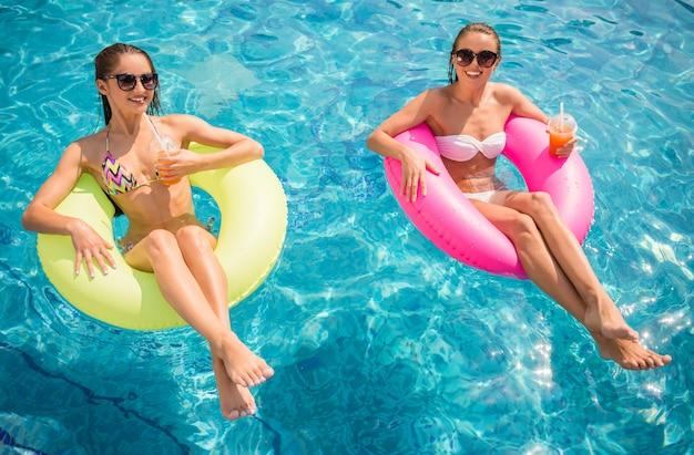 Namoradas alegres estão se divertindo na piscina. Foto Premium
