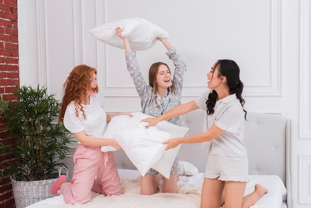 Namoradas brigando com almofadas Foto gratuita